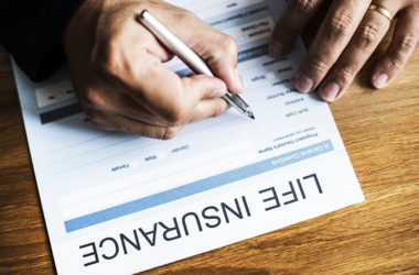 Close up of woman filling out life insurance form